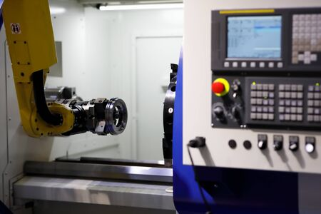Process of automatic loading detail into CNC lathe machine with the robot arm. Selective focus.