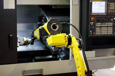 Robot arm is loading detail into CNC lathe machine. Selective focus. Reklamní fotografie