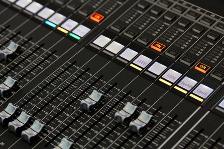 Controls of a digital sound mixing console. Selective focus.
