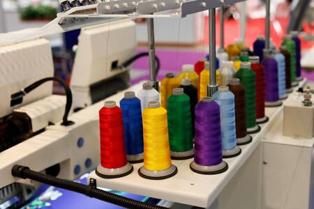Colored thread cones on stand attachment for embroidery machine. Selective focus.