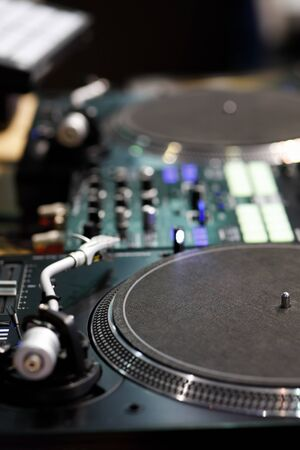 Professional DJ turntables and sound mixer. Selective focus.