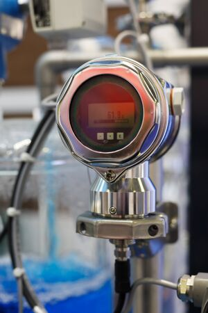 Industrial digital gauge measuring liquid flow at a chemical plant. Selective focus.