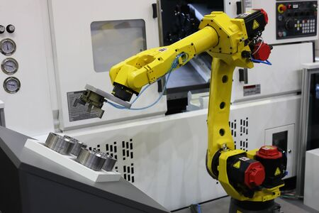 Automated CNC machine loading with robotic arm. Selective focus. Reklamní fotografie