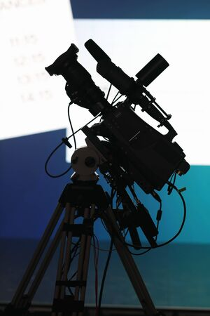 Professional TV camera on the tripod before news briefing. Reklamní fotografie