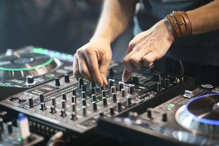 DJ using sound controller to mix music. Selective focus.
