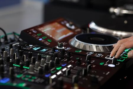 DJ using a sound mixer controller to play music. Selective focus. Reklamní fotografie