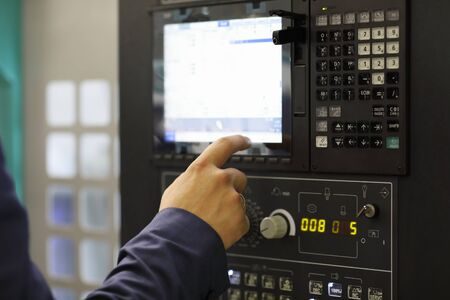 Engineer working with touchscreen on control panel of CNC machining center. Selective focus.