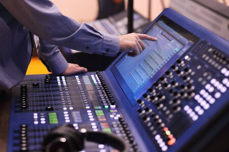 Operator working with digital mixing console using touch screen. Selective focus.