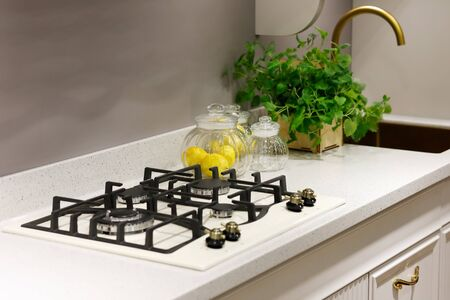 Modern kitchen counter with built-in 4 burner gas hob. Selective focus.