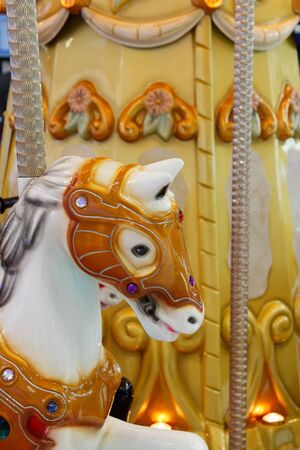 Head of a wooden horse on vintage style merry-go-round. Selective focus.