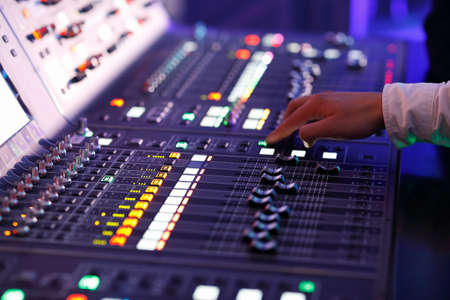 Sound engineer working with controls of a sound mixing console. Selective focus.