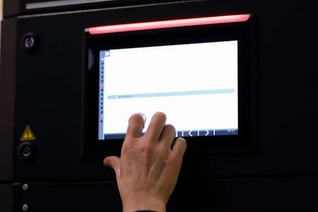 Working with a touch screen control panel of industrial equipment. Selective focus.