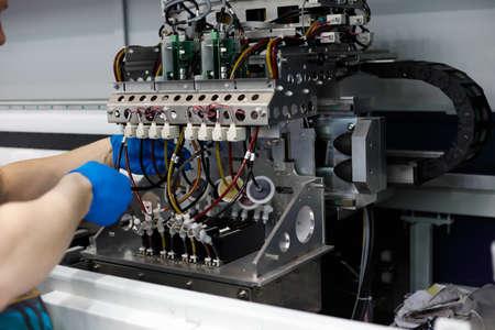 Male technician performs maintenance work on large format floor standing fabric printer. 版權商用圖片