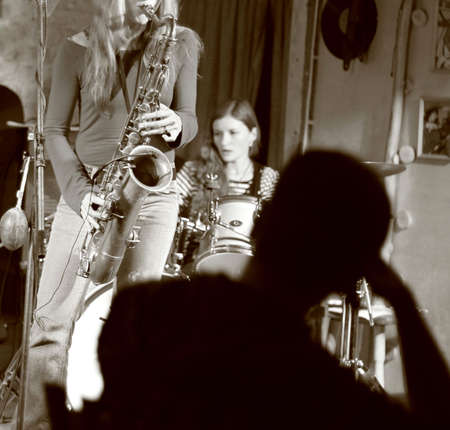 jazz band: The girl plays a jazz on a saxophone in small club Stock Photo