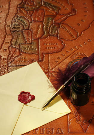 Still-life with a letter, a quill and an inkwell on a background of a map of South America photo