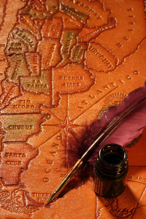 Still-life with a map of South America, a quill and an inkwell photo