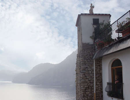 The girl looks at mountains and the sea from a window of hotel. Italy. Amalfi photo