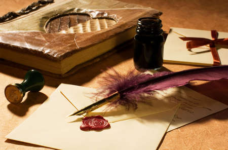 Love letters with a quill, an inkwell and a diary on a rustic paper.   photo