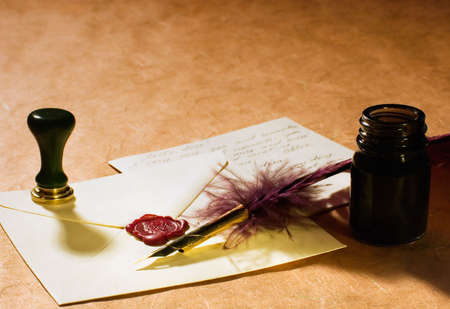 letter with a quill, an inkwell & a stamp on a rustic paper.  Stock Photo