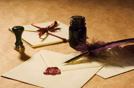 Letters with a quill, an inkwell & a stamp on a rustic paper.  photo