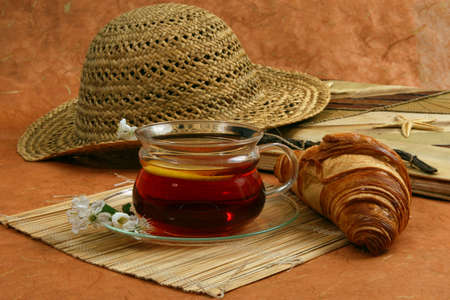comfy:  still-life with a croissant, a glass of tea, flowers, diary and a female hat