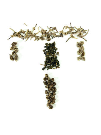 """The letter """"T"""" spelled out in green tea leaves."""