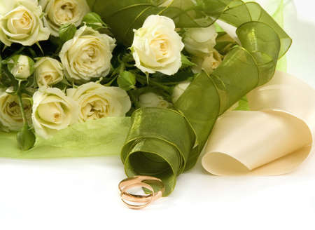 Wedding rings and roses on white background. photo