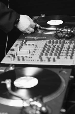 hand of the Dj Music, vinyl  record player and sound board sliders at nightclub. photo