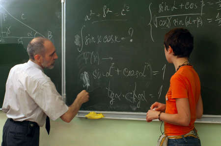 The teacher and the schoolgirl near blackboard. Lesson of mathematics Stock Photo - 3446526