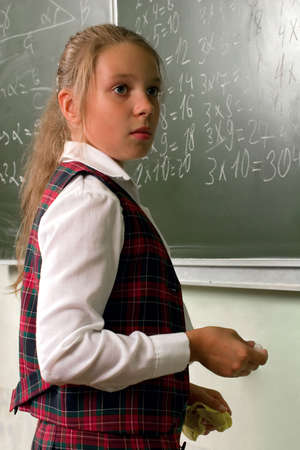 multiplication: Lesson. Schoolgirl at the blackboard. Writing  a multiplication table.