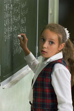 Lesson. Schoolgirl at the blackboard. Writing  a multiplication table. photo