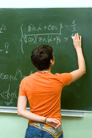 Lesson. Schoolgirl solves a mathematical problem  at the blackboard. photo