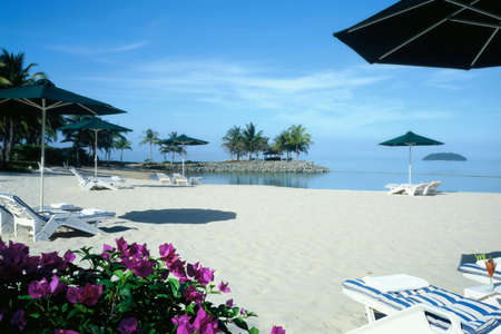 A tropical resort bay with white sand,  clear waters  and blue sky  photo