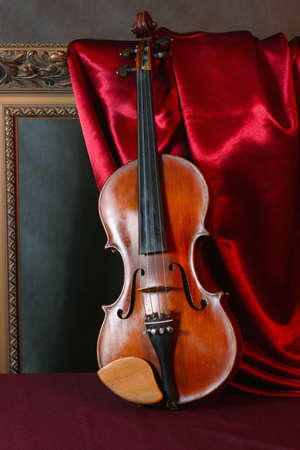 Still-life with a violin on red silk photo