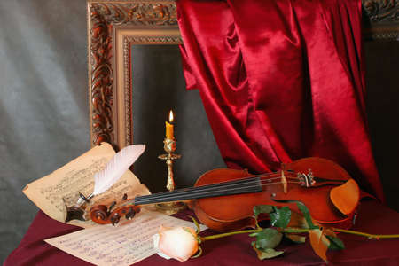 Romantic still-life with a violin, a flower and a music sheets   photo