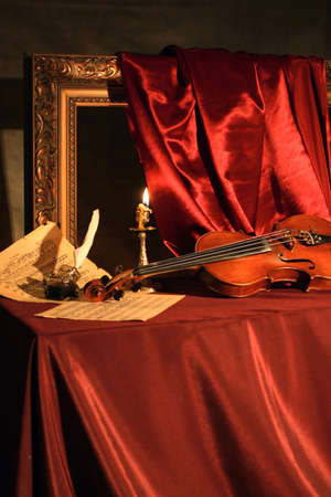 Classical still-life with a violin, a music sheets and  feather on red silk.