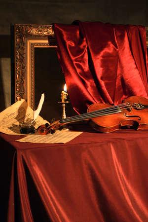 Klassiek stilleven met een viool, een muziek-bladen en veren op rode zijde. Stockfoto - 3682634