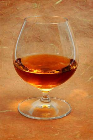 snifter: Snifter glass of  brandy  over vintage background.