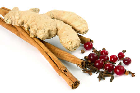 curative: Cinnamon, carnation, ginger root and cranberry on white background.Spices and berries for a curative drink. Stock Photo