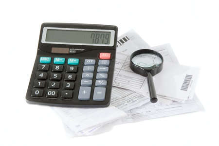 spendthrift: Calculator, bills and magnifying glass isolated on a white background. Planning  of family finances.