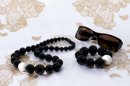 A female accessories - sunglasses, beads and  bracelet on stylish scarf  photo
