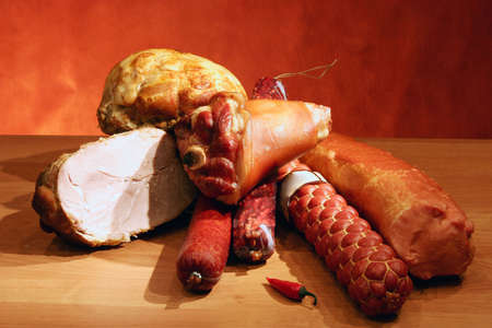 Still-life with various sausages and meats on wooden board.