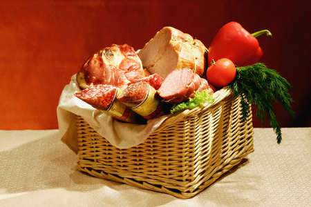 boiled sausage: Still-life with various sausages and meats with a vegetables in a basket.