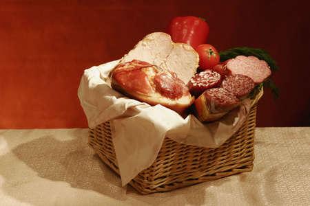 carnes y verduras: Naturalezas muertas con varios embutidos y carnes con verduras en una cesta. Foto de archivo
