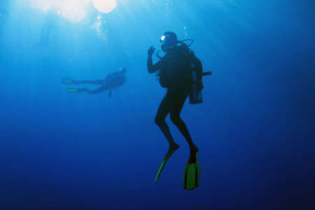diver: A scuba diver decompressing after dive. Surrounding waters are serene and penetrated by sun beams. Stock Photo