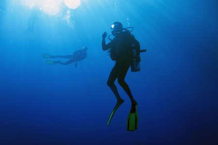 Un submarinista descomprimir después de bucear. Las aguas circundantes son serenas y penetraron por el sol vigas.