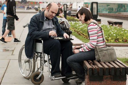 Woman and man on a wheelchair play chess in park