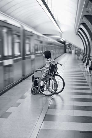 Young woman in wheelchair missed the train in subway. Stock Photo