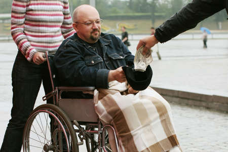 handout: Young man in wheelchair takes a handout from the stranger.