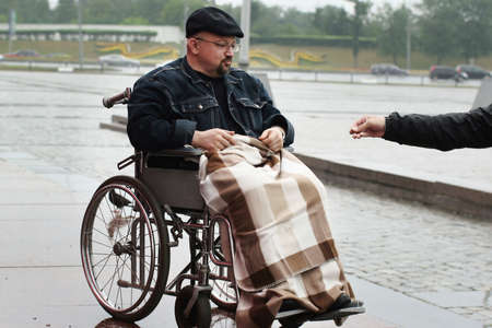 handout: Man in wheelchair takes a handout from the stranger.